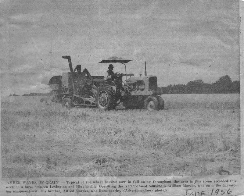 June 1956 - AMBER WAVES OF GRAINS - Typical of the wheat harvest now in full swing throughout the area in this scene recorded this week on a farm between Lexington and Higginsville. Operating the tractor-towed combine is William Marcks, who owns the harvesting equipment with his brother, Alfred Marcks, who lives nearby.